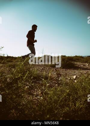 Seitenansicht eines Mann laufen im Feld - Stockfoto