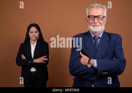 Ausgereifte multi-ethnischen Geschäft Paar gegen braunen Hintergrund - Stockfoto