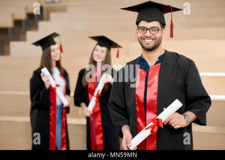 Glücklich lächelnde junge halten Universität Diplom. Absolvent in der Nähe von jungen groupmates und Suchen zufrieden. Die Studierenden tragen schwarz und rot gefärbte Graduierung Kleider. Ende der Universität. - Stockfoto