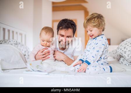 Stattliche Vater mit Kind Kinder im Schlafzimmer zu Hause, Geschichten lesen vor dem Schlafengehen. Vaterschaftsurlaub.