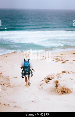 Frau Wanderer mit Rucksack auf einer Düne in Richtung der Lonely Beach. Sao Vicente Kap Verde - Stockfoto