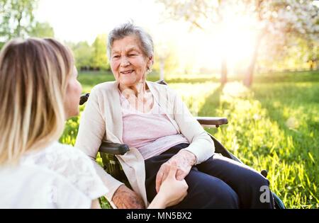Eine alte Großmutter im Rollstuhl mit einem erwachsenen Enkelin außerhalb im Frühling Natur, halten sich an den Händen. - Stockfoto