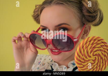Eine schöne, junge Mädchen, dass einen Lutscher in der Hand und nehmen Sie die große Gläser lenkt den Blick in die Kamera - Stockfoto