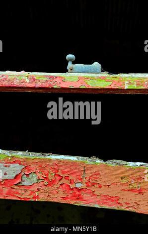 Abschnitt einer maroden Fenster Rahmen mit zerbröckelnden Peeling roter Farbe und Fenster fangen. - Stockfoto