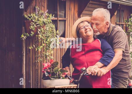 Gerne älteres Ehepaar in der Liebe bleiben zusammen auf einem Fahrrad outdoor Spaß haben und Küssen. Kaukasier, Erwachsene foreverness Paar in glücklich im Ruhestand leben von - Stockfoto