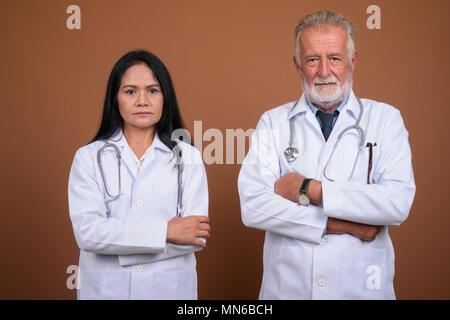 Ausgereifte multi-ethnischen paar Ärzte gegen braunen Hintergrund - Stockfoto