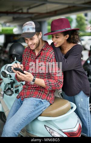 Lächelnd interracial Paare auf dem Parkplatz im Freien. Weißer Kerl in einem roten Hemd sitzt auf einem Motorrad und schaut auf sein Smartphone, schwarze Mädchen in einem cr - Stockfoto