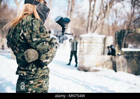 Weibliche paintball Spieler schießen auf den Feind, Blick nach hinten, Winter Forest Kampf. Extreme Sport Spiel, Spieler in Schutz Masken und Camouflage liegt auf - Stockfoto
