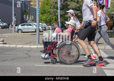 Belgrad, SERBIEN - 21. APRIL 2018: Behinderte Athleten in einem Rollstuhl Marathon, durch Läufer geholfen. 31 Belgrad Marathon - Stockfoto
