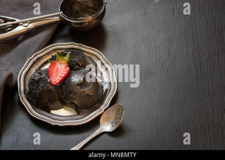 Schwarzes Eis in vintage Teller, garnieren frische Erdbeeren auf dem Schwarzen Brett. Platz für Text. - Stockfoto