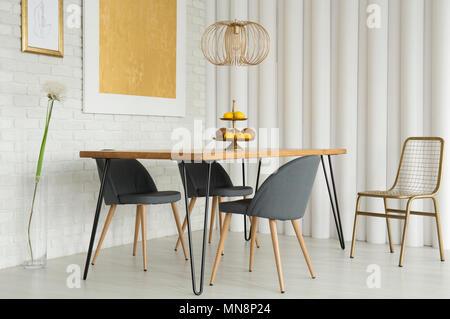 ... Einfache Esszimmer Interieur Mit Gold Malerei Auf Weiße Mauer Und  Grauen Stühlen An Einem Holztisch