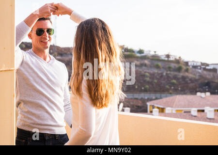 Lächeln und Glück tanzen im Freien auf der Terrasse. Paar in Liebe und Freundschaft Zusammen Spass haben auf der Dachterrasse mit Blick auf die Berge - Stockfoto