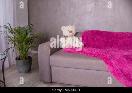 Teddybär - Sitzen auf einem Sofa Couch mit lila Decke Plaid. Palm Tree als Home Anlage ist in der Nähe von Sofa. Broun beige Teddybär, Soft Toy. Platz kopieren - Stockfoto