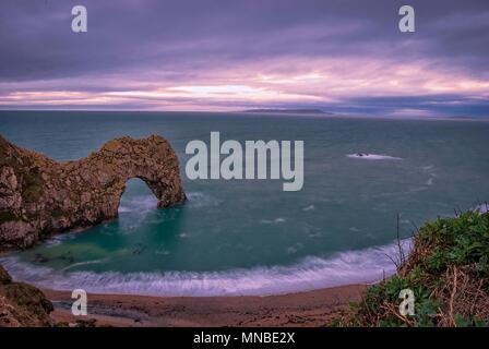 Die Sonne über dem Ärmelkanal an Durdle Door auf der Jurassic Coast in Dorset