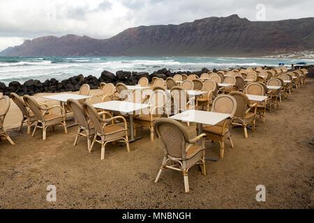 LANZAROTE, KANARISCHE INSELN, SPANIEN: Nebensaison - leere Tische und Stühle auf der Terrasse von Famara, mit dem Meer und Felsen im Hintergrund. - Stockfoto