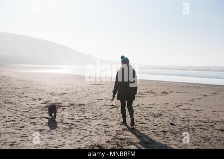 Eine Frau, die zu ihrem Hund auf Croyde Strand Devon