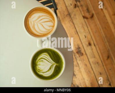 Zwei Tassen Matcha Tee und Cappuccino mit schönen latte Kunst auf grauen Farbe Tabelle. Stockfoto