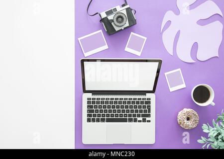 Kopieren Sie Raum und Laptop auf eine ultra violett unterlegt mit Fotos, Kaffee und Donut - Stockfoto