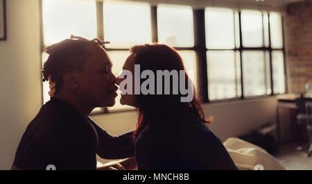 Zärtlich Paar über einander zu küssen im Schlafzimmer. Interracial Mann und Frau sitzt auf dem Bett und Küssen. - Stockfoto