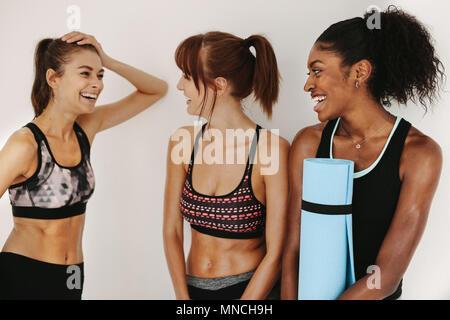 Junge weibliche Freunde Rest nach Fitness Training. Glückliche junge Frauen entspannen und Reden in der Turnhalle. - Stockfoto