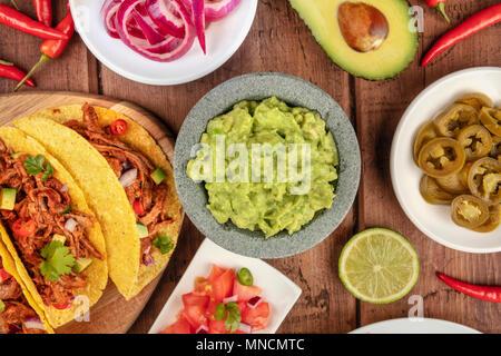 Ein Foto von einem ssortment vieler verschiedener mexikanische Lebensmittel, wie Tacos, Guacamole, Pico de Gallo, Jalapenos und andere - Stockfoto