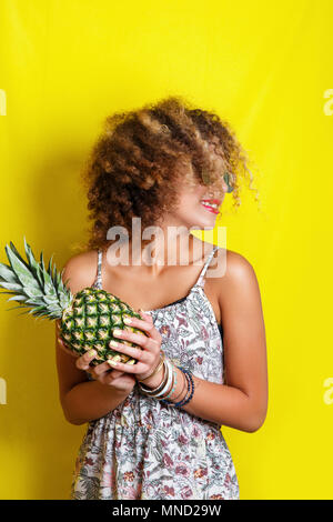 Beauty Portrait der jungen afrikanischen amerikanischen Mädchen mit Afro Frisur bei Sonnenbrillen. Mädchen mit Ananas auf gelben Hintergrund posiert, Studio gedreht. - Stockfoto