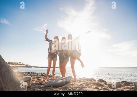 Gruppe von drei Schöne nette junge Frau springen für Spaß und Freude, unabhängiges Leben in Freundschaft. Teneriffa Stein Strand an einem sonnigen Tag - Stockfoto
