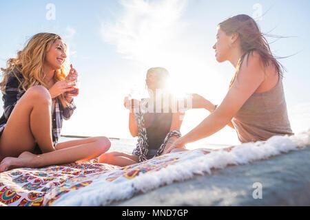 Gruppe von jungen Frauen Freund zusammen trinken Fruchtsaft auf einem Felsen am Strand auf Teneriffa. Beziehung für ein Team der Ferienhäuser und Glück zu EJOY.