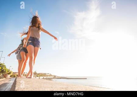 Drei junge Frauen, die Freunde gehen gemeinsam an einer Wand in der Nähe der Strand auf Teneriffa. Die Ferienhäuser unter einem blauen Himmel mit gelben Sonne genießen. Hände von den Händen. - Stockfoto