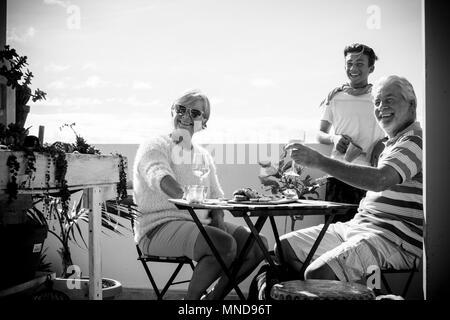 Ältere reifen Erwachsenen und ein Junge Aufenthalt auf der Terrasse Zusammen Spass haben. Ferienzeit Konzept mit Menschen genießen Sie die Ort - Stockfoto