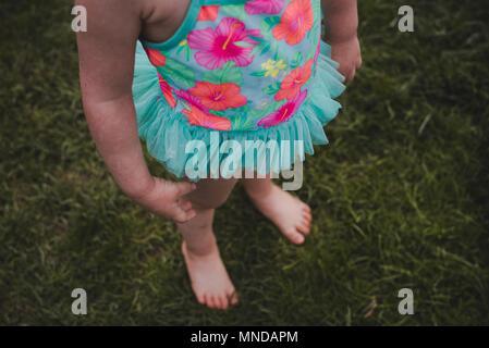 Eine gesichtslose Kleinkind Mädchen mit einem bunten Badeanzug mit Blumen. - Stockfoto