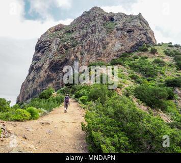 Eine weibliche Wanderer nähert sich Roque El Cano ein Basalt vulkanischen Plug hoch über der kleinen Stadt in Vallehermoso auf La Gomera auf den Kanarischen Inseln - Stockfoto