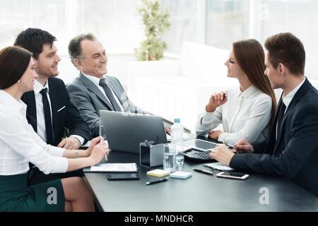Kollegen sprechen am Schreibtisch im Büro - Stockfoto