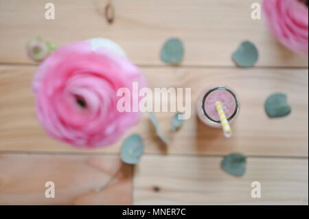 Himbeere Milch mit einem Stroh in einer Flasche und eine ranunculus Blume in einer Vase (von oben gesehen) - Stockfoto