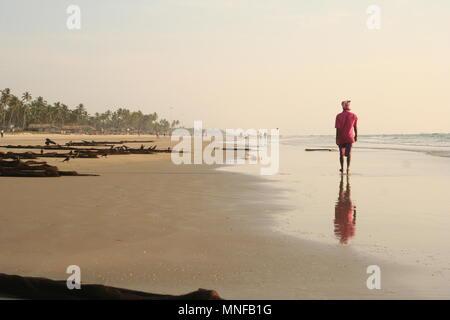 Mann in Rosa entlang Colva Beach mit Reflexion, Goa, Indien - Stockfoto