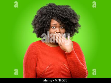 Schöne afrikanische Frau deckt Mund in Schock, blickt schüchtern, Stille und Fehler Konzepte, Angst - Stockfoto