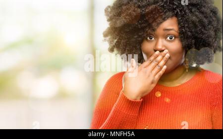 Schöne afrikanische Frau deckt Mund in Schock, blickt schüchtern, Stille und Fehler Konzepte, erschrocken, outdoor - Stockfoto