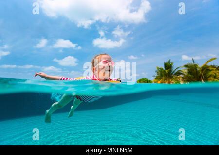 Split Unterwasser Foto der süßen kleinen Mädchen mit Gelb aufblasbarer Ring schwimmen in der Schwimmhalle im Sommerurlaub - Stockfoto