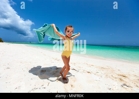 Süße kleine Mädchen Spaß mit Handtuch und geniessen Urlaub auf tropischen Strand mit weißem Sand und türkisfarbenem Meer Wasser - Stockfoto