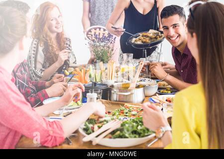 Glückliche Menschen kochen und gemeinsam essen Vegetarisches frische Mittagessen auf der Startseite - Stockfoto