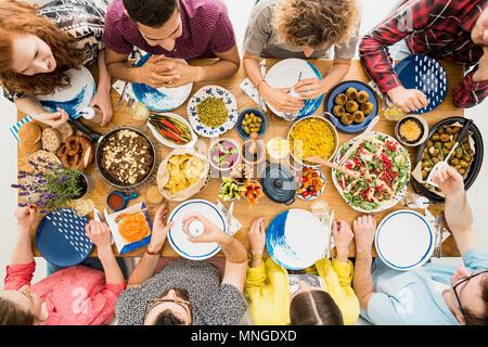 Rothaarige Frau und ihre Freunde genießen Sie vegetarisches Treffen mit gesunden Lebensmitteln Stockfoto