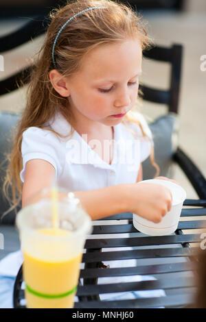 Kleines Mädchen essen ein Eis im Café im Freien