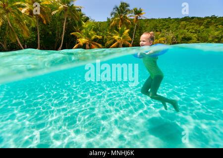 Split Unterwasser Foto der süßen kleinen Mädchen mit blauen aufblasbaren Ring schwimmen im tropischen Ozean im Sommerurlaub - Stockfoto