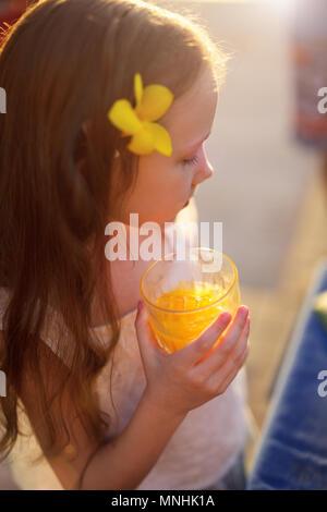 Adorable kleine Mädchen trinken Saft aus einem Glas - Stockfoto