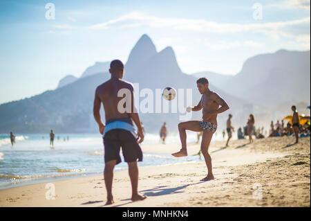 RIO DE JANEIRO, BRASILIEN - ca. März 2018: Junge Brasilianer spielen Sie eine Partie Fußball Keepy Uppy'-altinho' am Ufer des Ipanema Beach. - Stockfoto