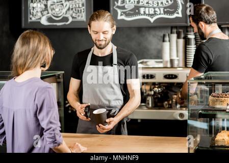Stattliche barista die Zubereitung von Kaffee für eine junge Frau, die Kunden am Counter der Coffee Shop - Stockfoto