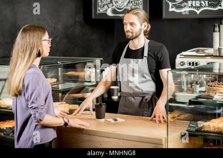 Stattliche barista mit junge Frau Kunden am Counter der Coffee Shop - Stockfoto
