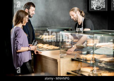 Junges Paar kaufen Kaffee stehen mit den stattlichen Barista in der modernen Coffee Shop - Stockfoto