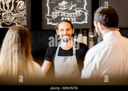 Stattliche Barista im Gespräch mit jungen Geschäft Paar an den Zähler der Coffee Shop - Stockfoto