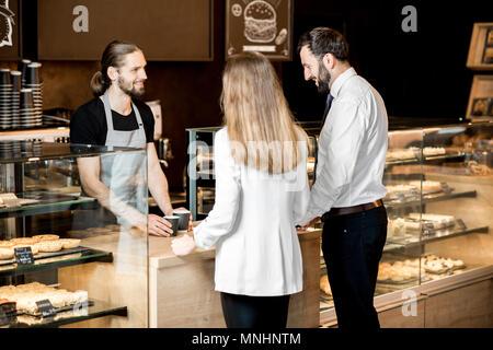 Young Business Paar kaufen Kaffee stehen mit den stattlichen Barista in der modernen Coffee Shop - Stockfoto